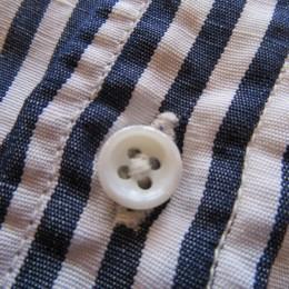 生地に合わせて白に染色した貝ボタンが使われています。